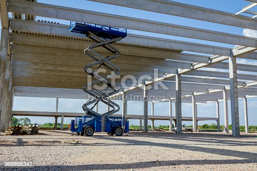 Scissor lift platform with stretched hydraulic system at maximum height range under building skeleton.