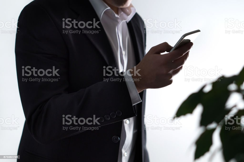 Mobile security, phisning and online crime. Businessman or man in a suit holding a smartphone in dark shadow. stock photo