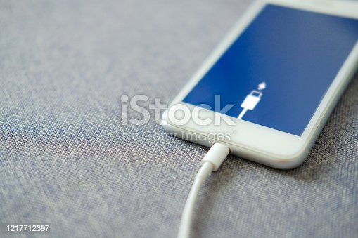 Smartphone fast charging using USB cable. Selective focus with blurry fabric background.