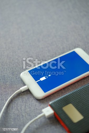 Smartphone fast charging using USB cable from powerbank. Selective focus with blurry fabric background. On the move recharging solution