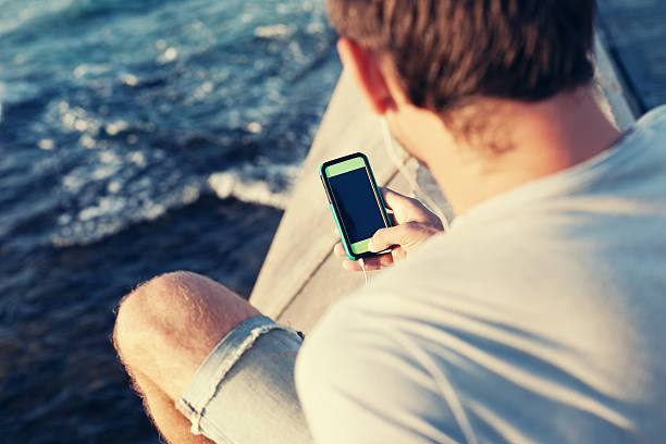 mobile smartphone in der hand der mann in der nähe von meer - nachrichten video stock-fotos und bilder