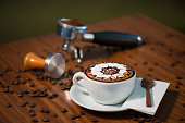mocca coffee in the white mug on the wooden table with coffee beans
