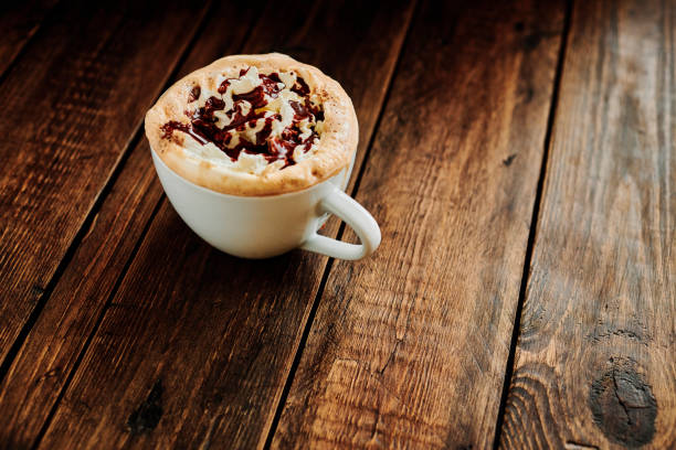 Mocha Coffee topped with whipped cream and chocolate sauce served on a rustic wooden table. stock photo