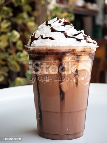 Mocha frappe in plastic cup. Served with whipping cream and chocolate sauce. Freshness drink. Favorite caffeine beverage.
