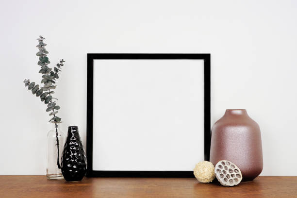 Mock up black frame with home decor and eucalyptus branch on a wood shelf against a white wall stock photo