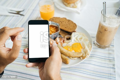 Mock up, black Smartphone in hand on a light food background. Calorie counting, weight tracking, and calorie foods. American breakfast: Fried eggs with sausages, tomatoes, bacon, and toasted bread.