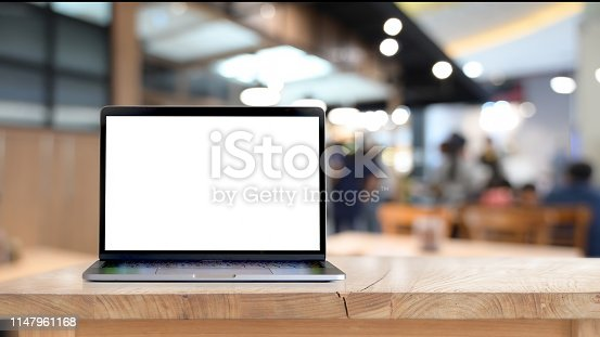 Mock up blank screen laptop on wood table