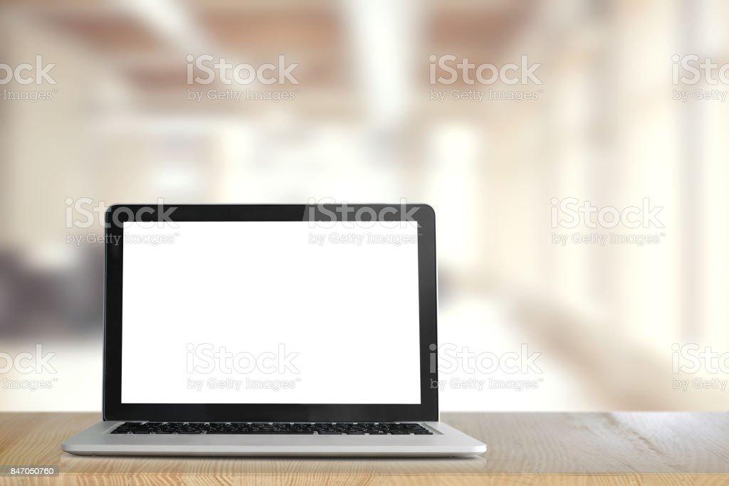 小樣的筆記本電腦在共同工作或辦公室的木桌上的空白螢幕。圖像檔