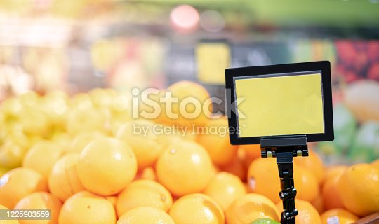 Mock up blank sign price tag display in supermarket Interior, apple basket. Retail fresh supermarket for people shopping in the blur background concept.