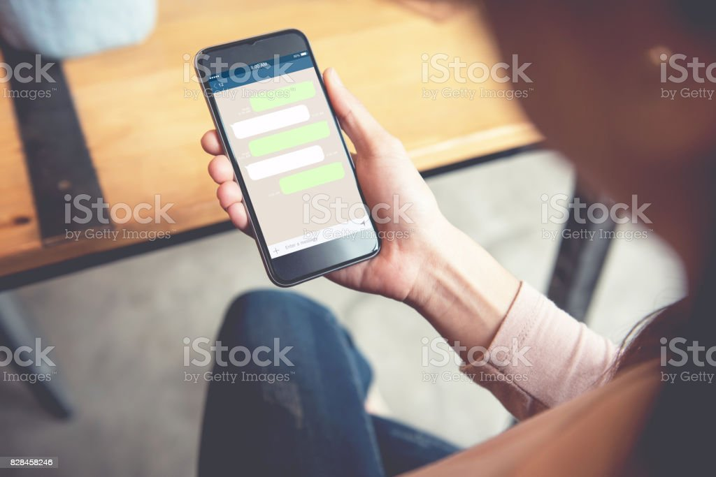 Closeup woman hand holding smart phone, Mock up Blank template chat...