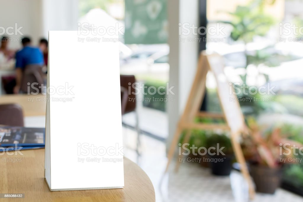 Mock up blank template menu frame on wood table in restaurant with blurred background, Clipping path included stock photo