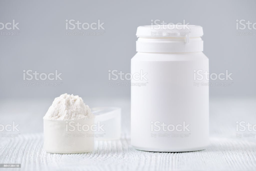 mock up bottle and a spoon with powder, selective focus, on gray stock photo