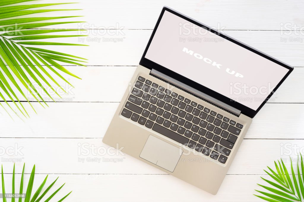 Mock up display of laptop on white wooden table for Summer Holiday...