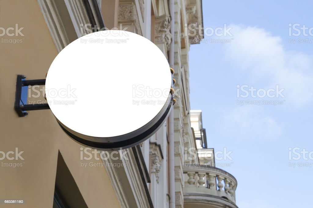 Mock up. Empty round signboard on classical architecture building. stock photo