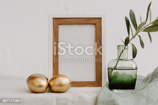 922658520 istock photo Mock Up Happy Easter. Gold eggs, frame and olive brunch over Linen Rustic Background 937117284