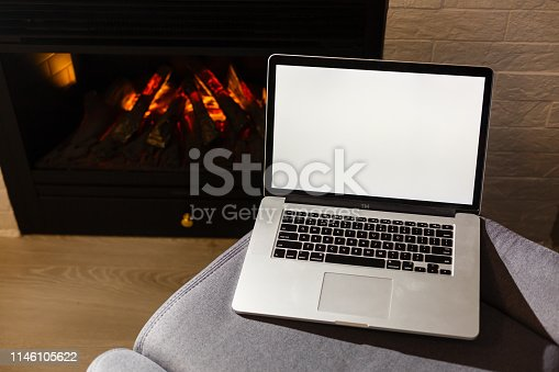 Mock up image of business man using and typing on laptop with blank white screen , sitting at indoor with fireplace background. Copy Space for text area
