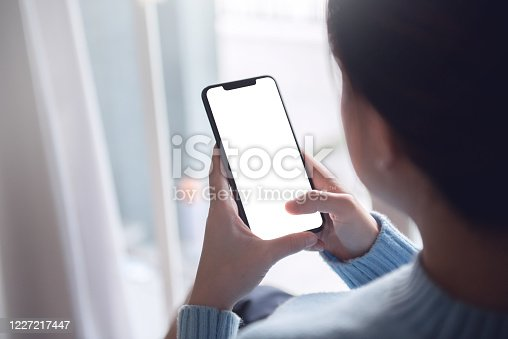 Mock up image of hand touching mobile smartphone with blank white screen in home interior, living room, copy space.