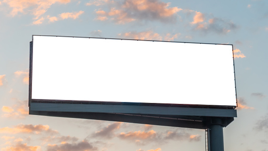 Mock up image: wide blank white billboard or large display and clouds against sunset warm sky. Consumerism, mockup, advertising, isolated white screen, background, template, copyspace concept