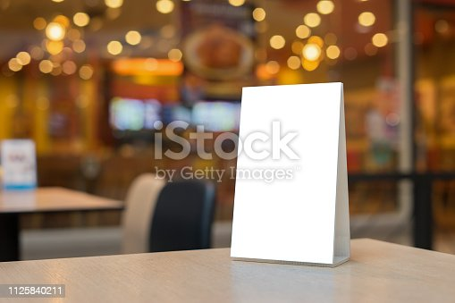 Mock up Label the blank menu frame in Bar restaurant ,Stand for booklets with white sheets paper acrylic tent card on wooden table cafeteria blurred background can inserting the text of the customer.