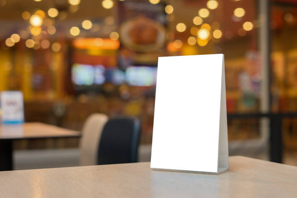 mock up label the blank menu frame in bar restaurant ,stand for booklets with white sheets paper acrylic tent card on wooden table cafeteria blurred background can inserting the text of the customer. - vinyl banner mockup stock photos and pictures