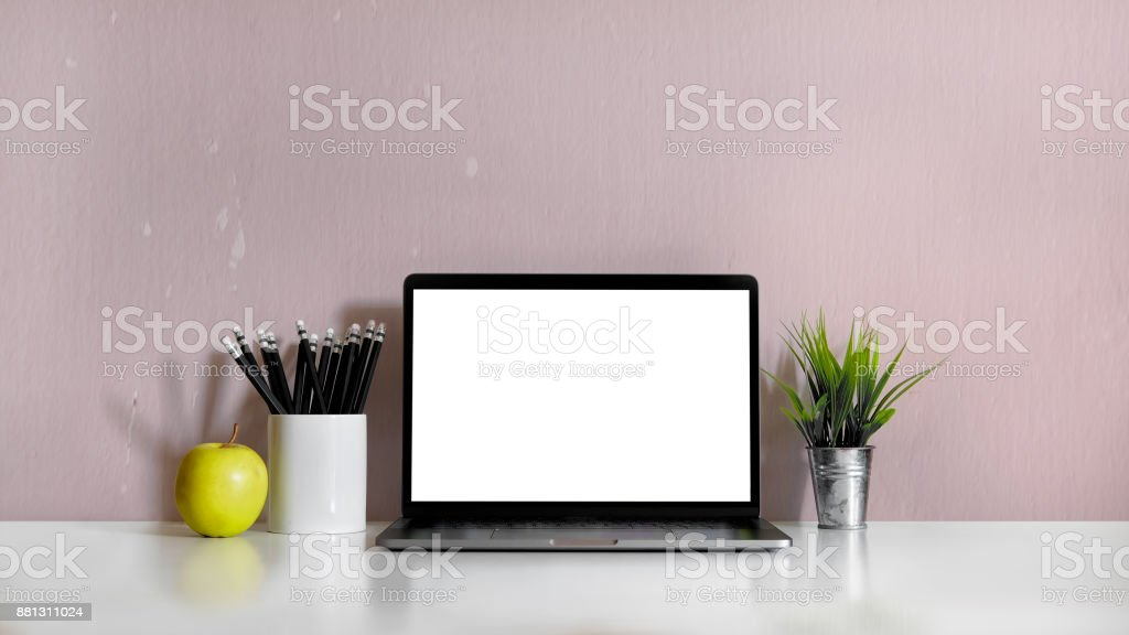 Work space desktop with blank white laptop, pencils and stationery...