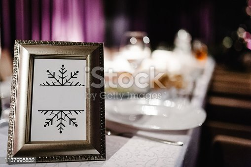 istock Mock up. Menu frame on table in restaurant. Blank blackboard. Stand for booklets with white sheets of paper, tent, card on cafeteria, blurred. Close up. Place for text. 1137995832