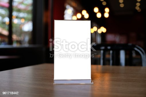 istock Mock up Menu frame standing on wood table in Bar restaurant cafe. space for text 961718442
