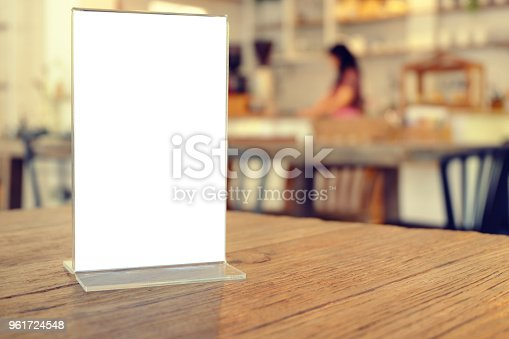 istock Mock up Menu frame standing on wood table in Bar restaurant cafe. space for text 961724548