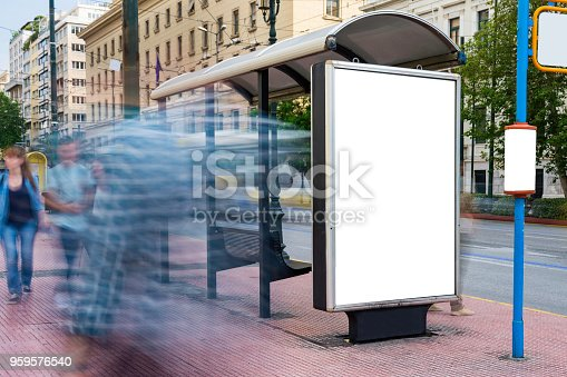 1051623396istockphoto Mock up of blank white vertical bus stop in a city with blurred people 959576540