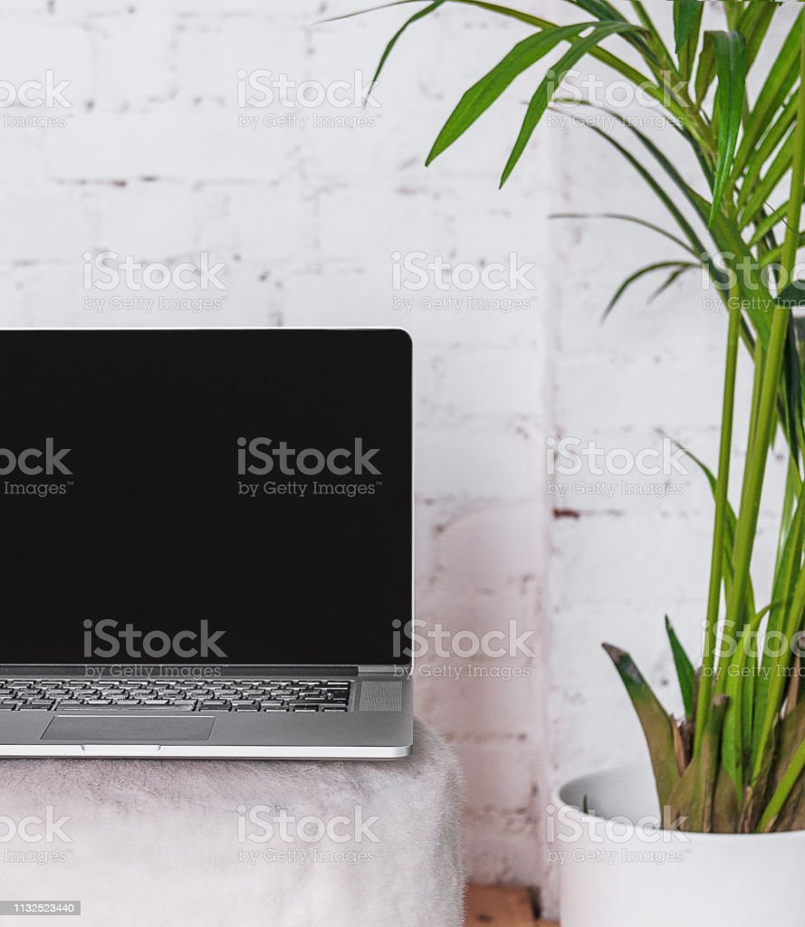 Mock up of laptop with blank black screen on the chair