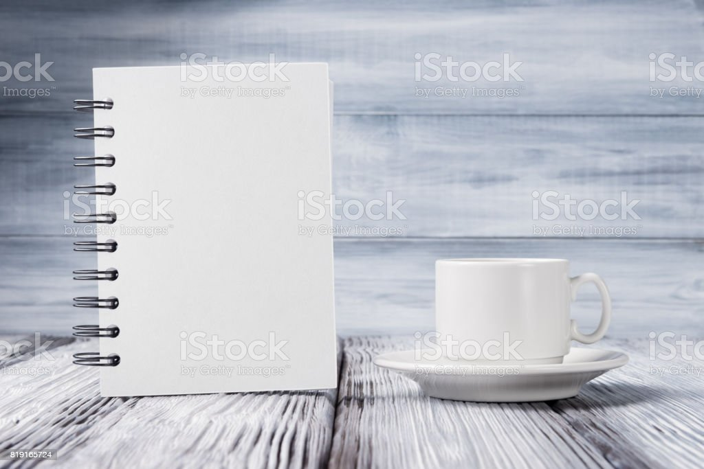 Mock up of sketchbook and coffee cup over light wooden background stock photo