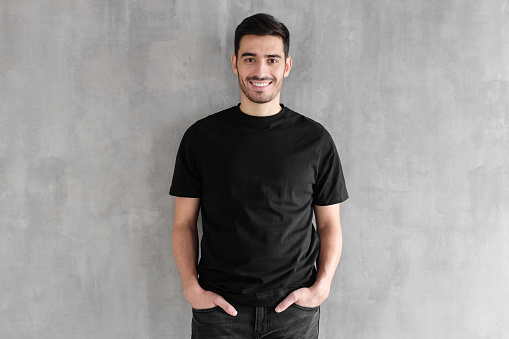 istock Mock up of young man body in empty black t-shirt isolated on textured gray wall background 1090883136