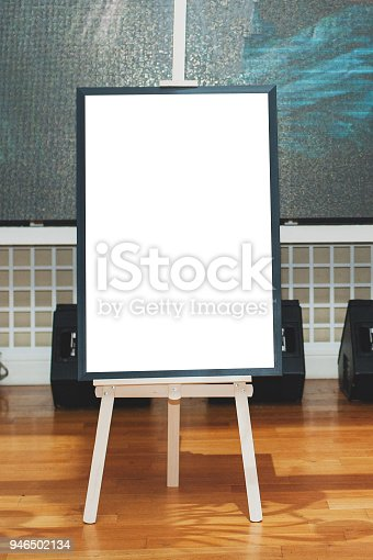 istock Mock up - painting on an easel at an exhibition or auction. Vertical photo. 946502134