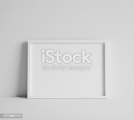 istock Mock up poster with white frame close up near wall 1272852141