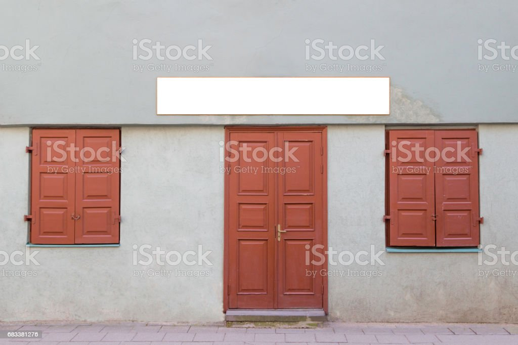 Mock up signboard on facade of the old house with old wooden door and two closed windows. stock photo