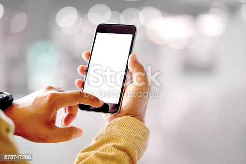 istock Mock up smartphone blank screen in man hands in blurred office interior background. 873747286
