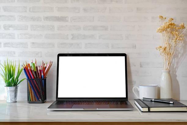 mock-up: stilvolle arbeitsbereich mit laptop-computer, büromöbel und bürobedarf, zimmerpflanze und bücher zu hause oder studio. leere anzeige für grafiken montage. - schmaler tisch stock-fotos und bilder