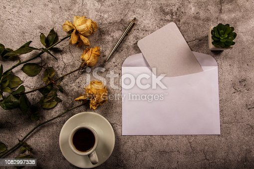 Mock up template with wilted flowers of white roses with a clean envelope, notepad and cup of coffee on a gray concrete background. View from above. Flat lay. Template layout for designer.