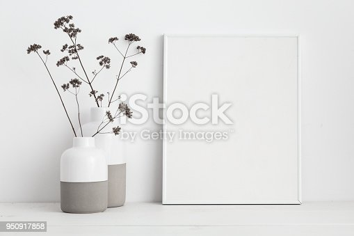 istock Mock up white frame and dry twigs in vase on book shelf or desk. White colors. 950917858