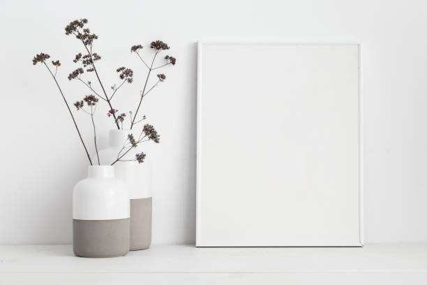 mock-up weißen rahmen und trockene zweige in die vase auf bücherregal oder schreibtisch. weiße farben. - desktop foto stock-fotos und bilder