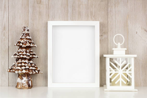 Mock up white frame with Christmas tree and lantern decor on a shelf against a rustic gray wood wall stock photo