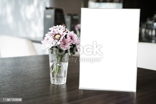 istock Mock up white Label for blank menu frame in restaurant cafe with plant flower. Stand booklet sheets paper tent card on table cafeteria display your product  background insert  text of customer. 1136700938