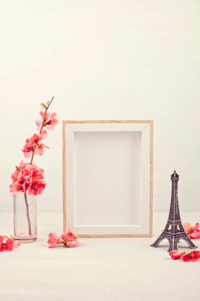 mit leerem bilderrahmen und rosa frühlingsblumen aufschlagen. - französisches haus dekor stock-fotos und bilder