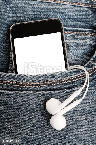 istock Mock up with modern  smartphone and earphones in jeans pocket. 1137421066