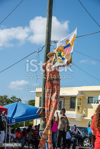 Frederiksted, St. Croix, US Virgin Islands-January 4,2020: Caribbean parade in downtown Frederiksted with mocko jumbie stilt walker carrying flag and spectators on the west end of St. Croix.