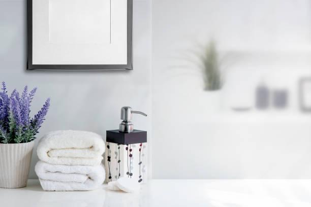 Toalla de baño de Mockup con botella de jabón líquido y planta de casa en mesa blanca en habitación blanca. - foto de stock