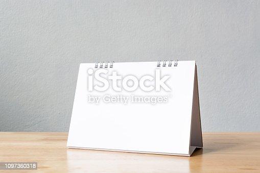 istock Mockup blank desk calendar on wood table. Template for design 1097360318