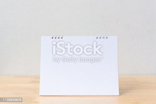 istock Mockup blank desk calendar on wood table. Template for design 1125633626