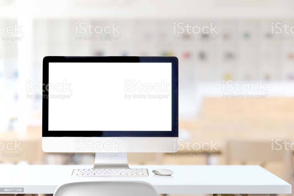 Mockup blank screen desktop computer on white wood table in co-working space. royalty-free stock photo