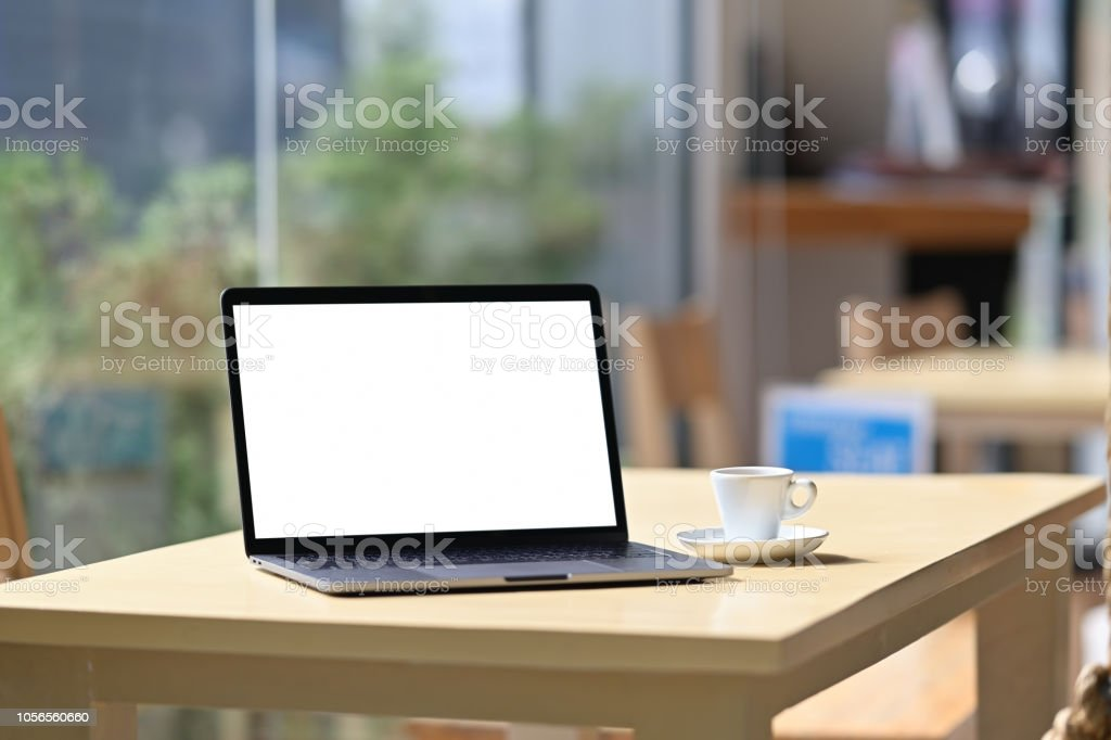 Mockup blank screen laptop on table in cafe background.